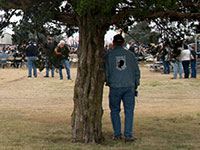 Man standing alone under tree watching ceremony, back of jacket says POW MIA
